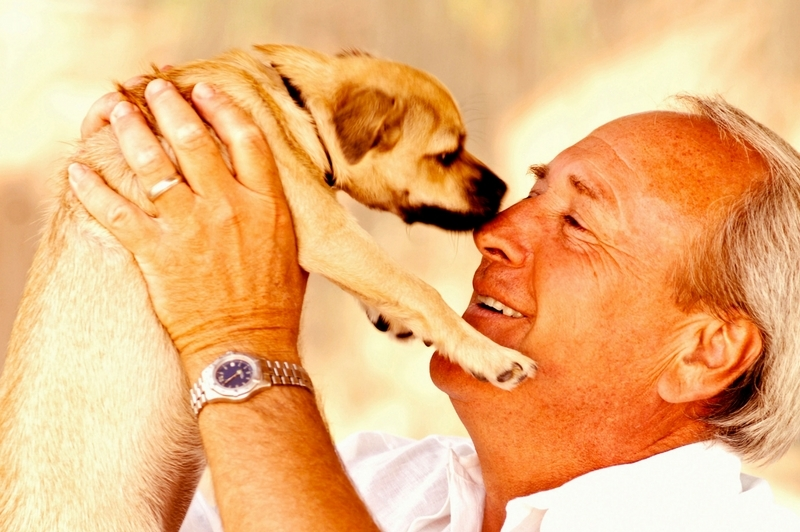 older man letting a puppy lick his nose