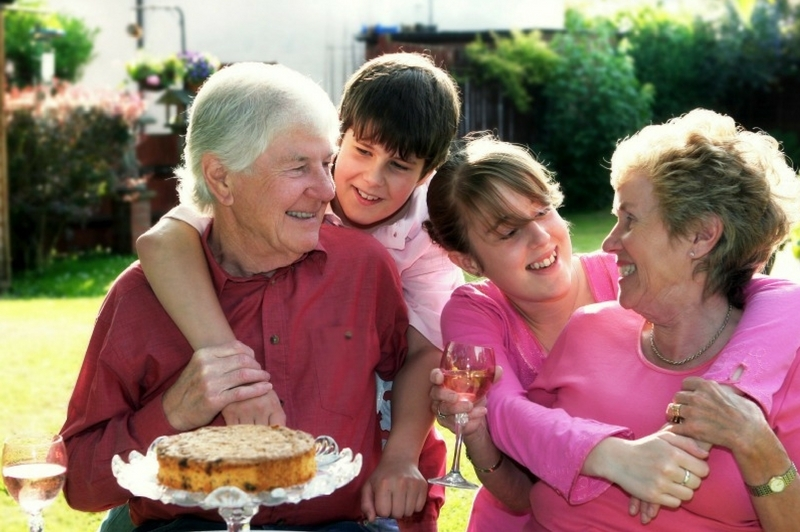 Grandparents enjoying some cake and sunshine with their grandchildren.