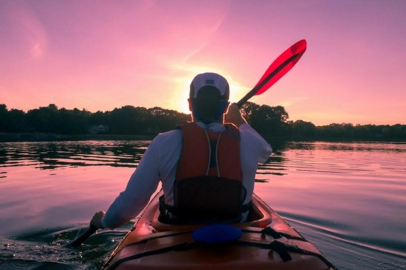 Man kayaking on a lake at sunset