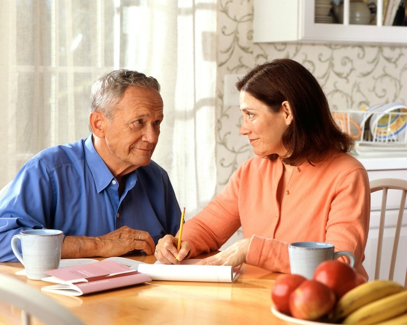 An older couple sitting an a kitchen making notes.