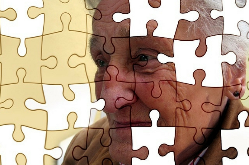 An older lady portrayed as a jigsaw puzzle with pieces missing.