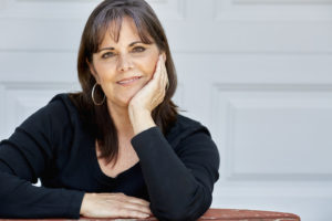 Happy middle aged woman smiling looking towards camera with her chin in her hand