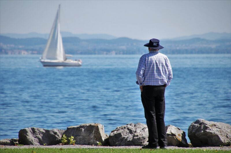 Man watching sailboat at a lake.